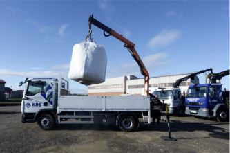 A handebag being lifted onto the back of a pickup truck